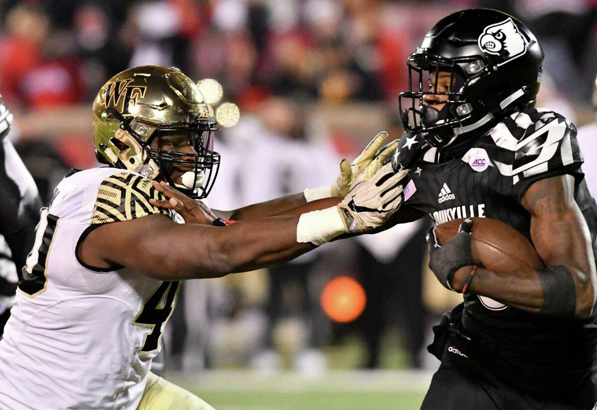 Wake Forest's Josh Banks (40) attempts to grab Louisville's Lamar Jackson (8) during the second half of an NCAA college football game Saturday, Nov. 12, 2016, in Louisville Ky. Louisville won 44-12. (AP Photo/Timothy D. Easley)