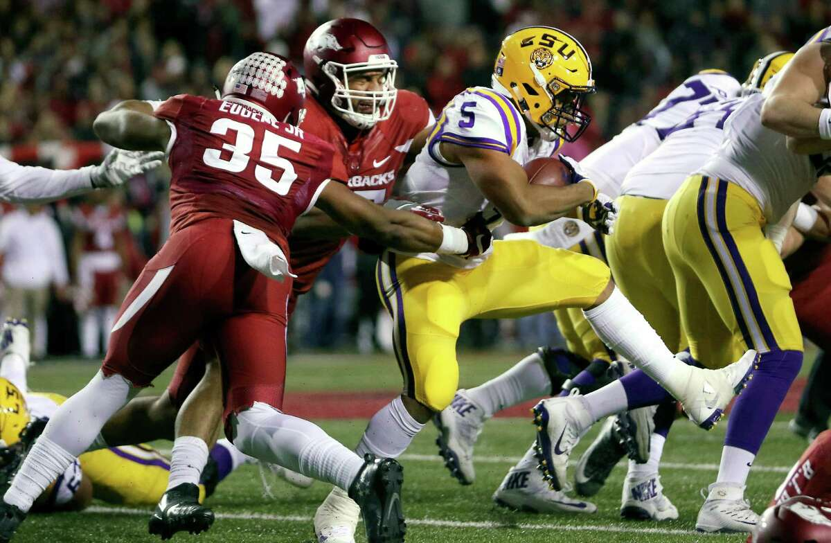 Arkansas' Dwayne Eugene (35) and Devin Buckner pull back LSU's Derrius Guice (5) during the first half of an NCAA college football game Saturday, Nov. 12, 2016, in Fayetteville, Ark. (AP Photo/Samantha Baker)