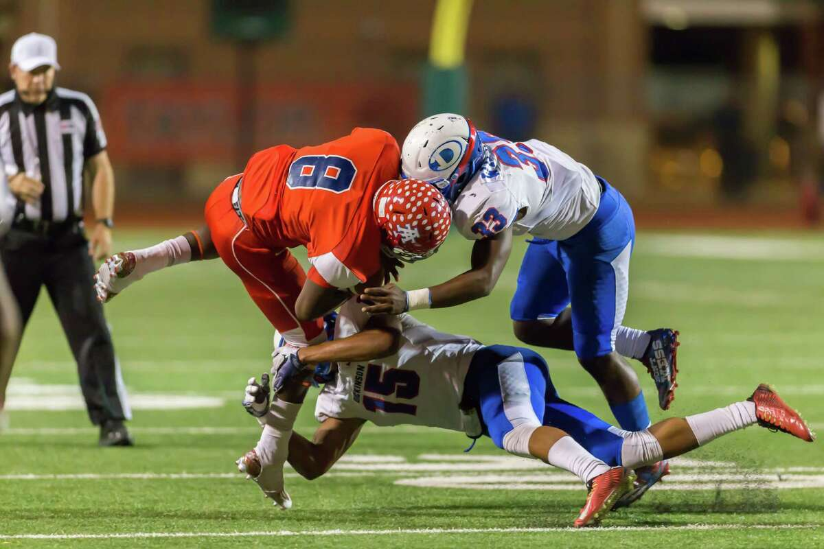 Dickinson Gators Trevor Harmanson (15) and Dickinson Gators A.j. Williams (33) tackle Alief Taylor Lions Dontay Warren (8) in the fourth quarter of the 6A Division 1 playoff game between Alief Taylor and Dickinson at LeRoy Crump Stadium on November 12, 2016 in Houston, Texas. (Leslie Plaza Johnson/Freelance)