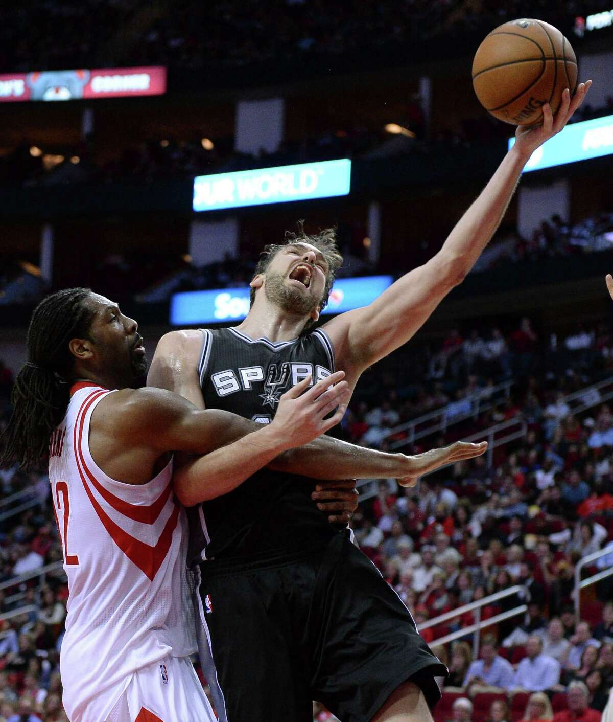 The Spurs' Pau Gasol, right, lets it be known he has been fouled by Rockets center Nene in the second half Saturday night. Gasol finished with 15 points.