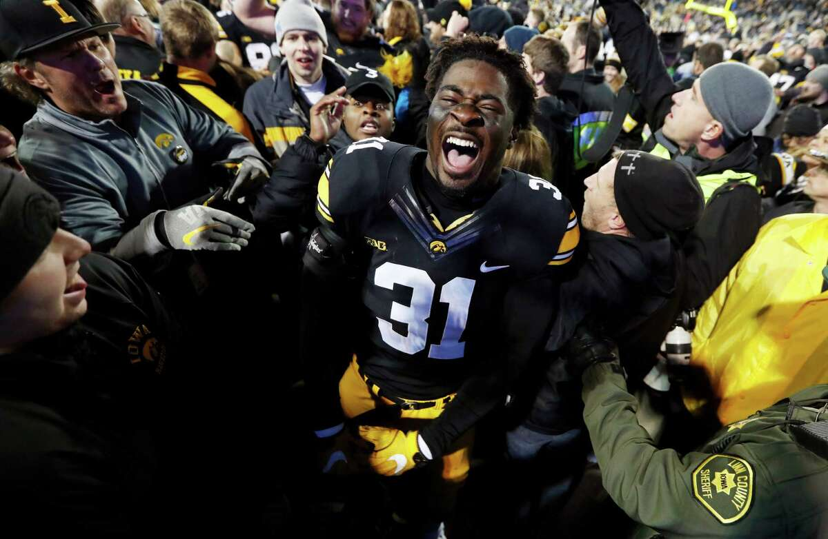 Iowa's Aaron Mends savors the moment with fans after the Hawkeyes upset Michigan on Saturday at Iowa City.