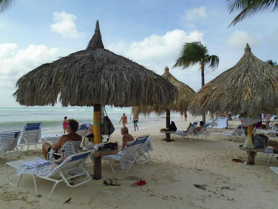 Relax beneath a thatched umbrella between swims in the Caribbean Sea in front of the Aruba Marriott. Photo: Robin Soslow / For The Express-News / Copyright 2009