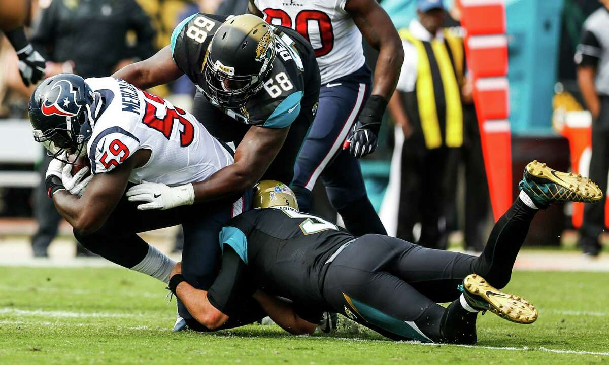 Houston Texans outside linebacker Whitney Mercilus (59) is tackled by Jacksonville Jaguars tackle Kelvin Beachum (68) after coming down with an interception during the second quarter of an NFL football game at Everbank Field on Sunday, Nov. 13, 2016, in Jacksonville.