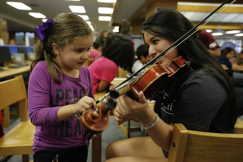 MacArthur High School senior Mariana Casillas (right) smiles as Luvia Rico plays a note on her violin during MacTeach on Tuesday, Oct. 25, 2016. The high school students give of their time to help tutor students from area elementary schools including some international refugees and their families. 146 MacArthur students tutor around 300-400 younger children. The program is in its seventh year and is overseen by English teacher Steve Davidson who gives all the credit to his tutors who work with the kids on Tuesdays and Thursdays. Davidson believes the tutors receive as much satisfaction or more than the students they help. Photo: Kin Man Hui, Staff / San Antonio Express-News / © 2016 San Antonio Express-News