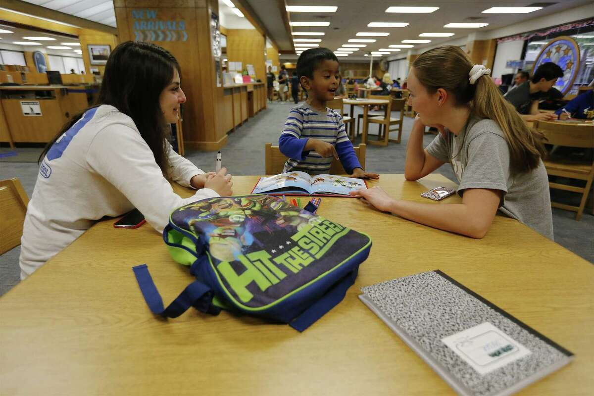 Three-year-old Tafser Howlader (center) gets reading help from MacArthur High School student tutors Angela Enriquez (left) and Alyssa Ramirez, both sophomores, during MacTeach where students give of their time to help tutor students from area elementary schools including some international refugees and their families. 146 MacArthur students tutor around 300-400 younger children. The program is in its seventh year and is overseen by English teacher Steve Davidson who gives all the credit to his tutors who work with the kids on Tuesdays and Thursdays. Davidson believes the tutors receive as much satisfaction or more than the students they help.