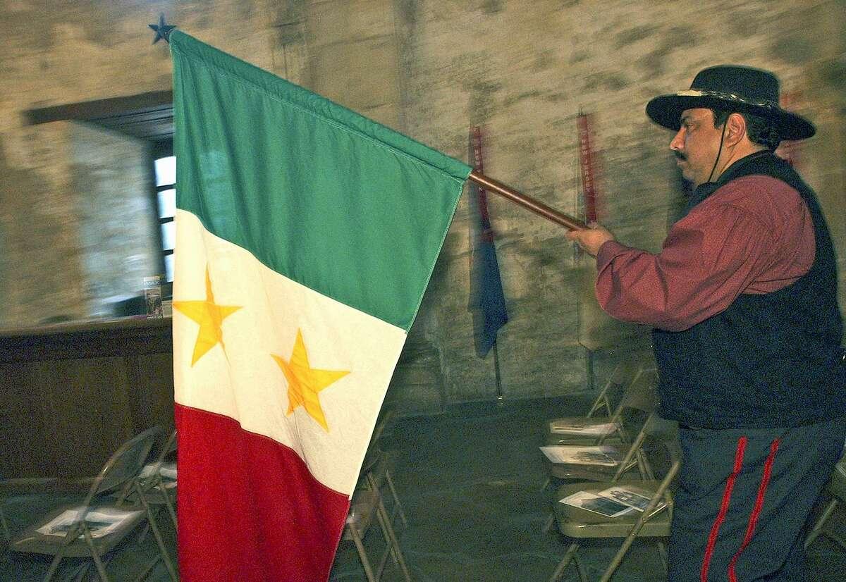 Rick Kidder walks a Tejano flag into the Alamo chapel to start a ceremonial vigil in 2005.