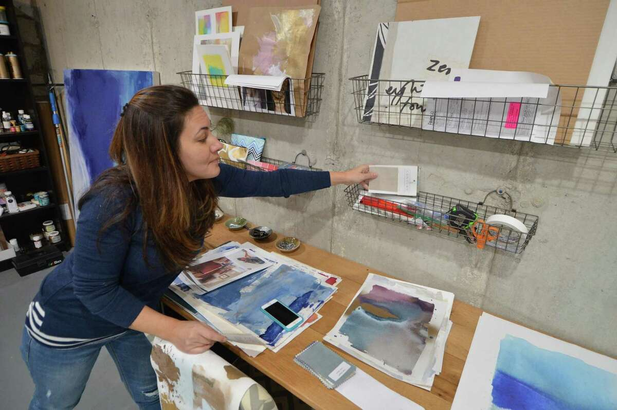 Artist Julia Contacessi grabs some color swatches from a client in her studio on Tuesday November 1, 2016 in Norwalk Conn