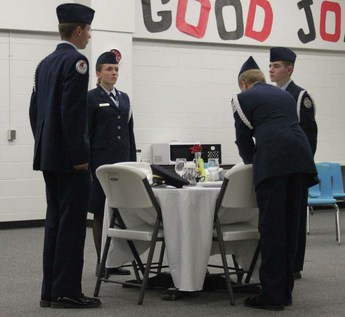 Four Coldspring-Oakhurst CISD JROTC cadets place hats from the four major branches of the United States military on a table set for POWs and MIAs.