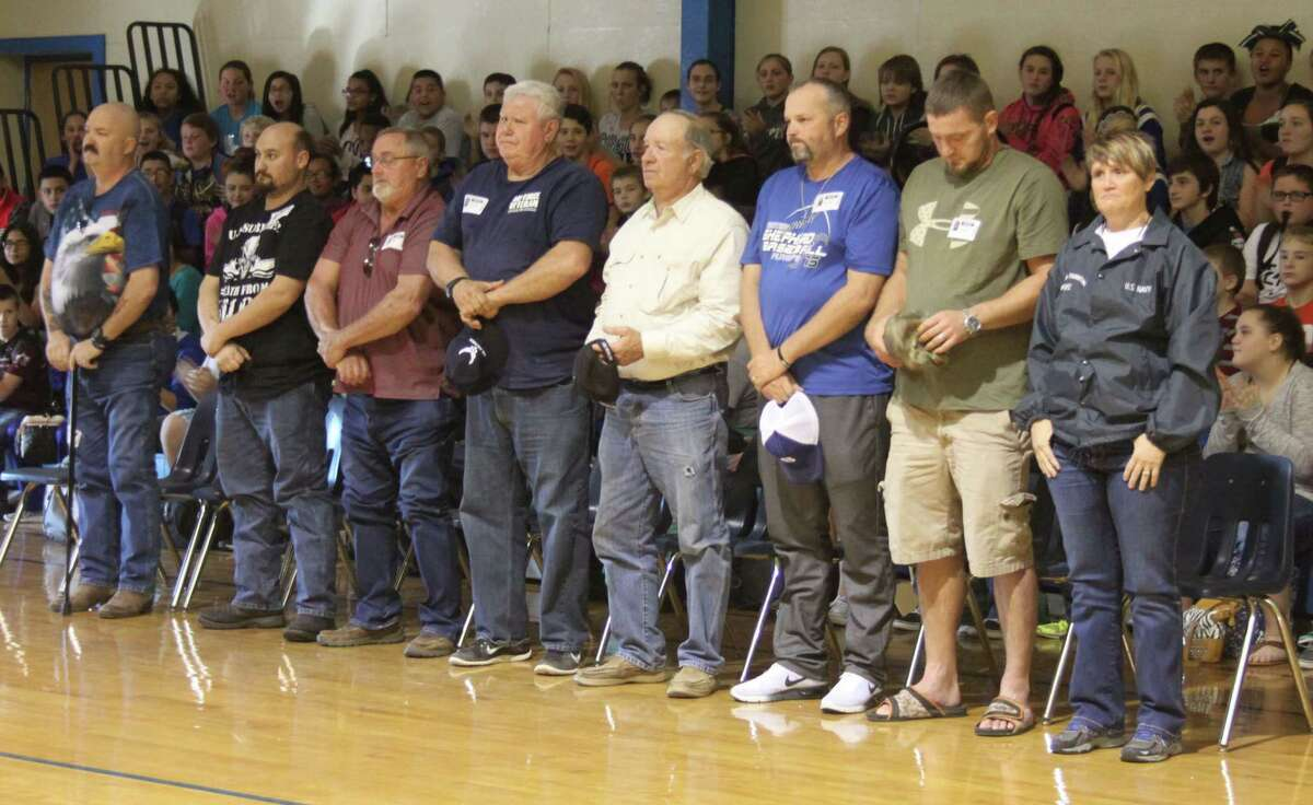 Veterans attending the Shepherd Middle School Veterans Day program stand up to be recognized by students.