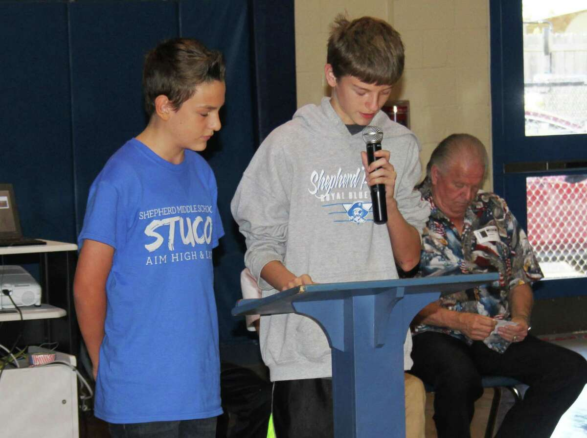 Austin Atchley (left) and Garret Cones (right) speak on the meaning of Veterans Day and why it is celebrated during the Shepherd Middle School Veterans Day program.