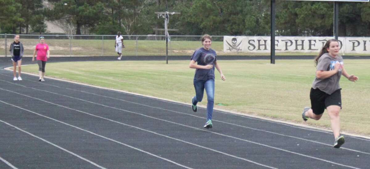 Two Shepherd ISD National Honors Society students decide to break into a run and leave their fellow classmates in the dust during the Walk for our Warriors fundraiser.