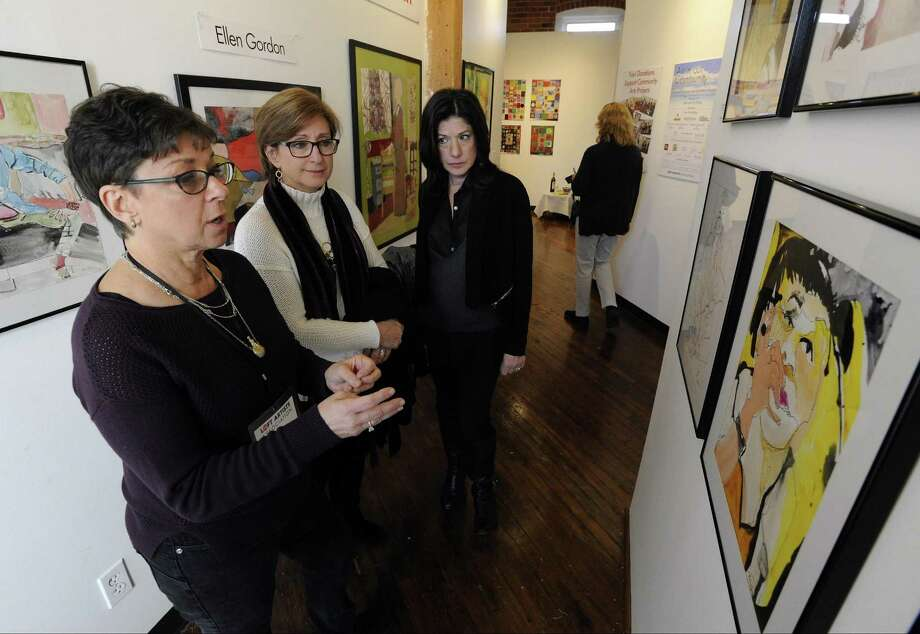 Ellen Gordon, left, an artist and president of the Loft Artists Association, talks about a painting  during the annual Open Studio event on Saturday. Photo: Matthew Brown / Hearst Connecticut Media / Stamford Advocate