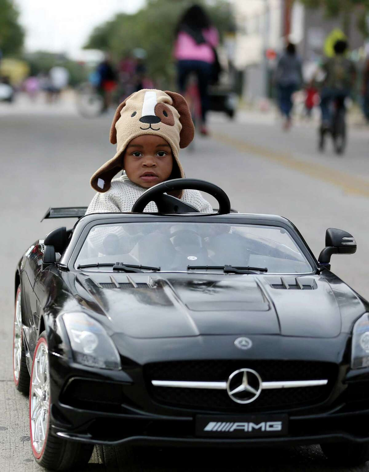 Reese Norman, 1, rides his remote parental control car controlled by his father, Ronald Norman, going down Lyons Avenue at Cigna Sunday Streets in Fifth Ward Sunday, Nov. 13, 2016, in Houston.