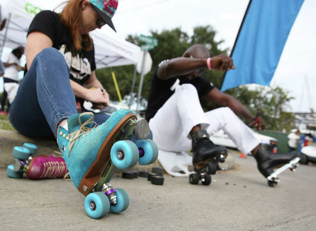 """In this photo: Tawnya """"T"""" King, left, and Leo """"Skate King"""" Butler change skates at the Sunday Streets in Fifth Ward in 2016."""