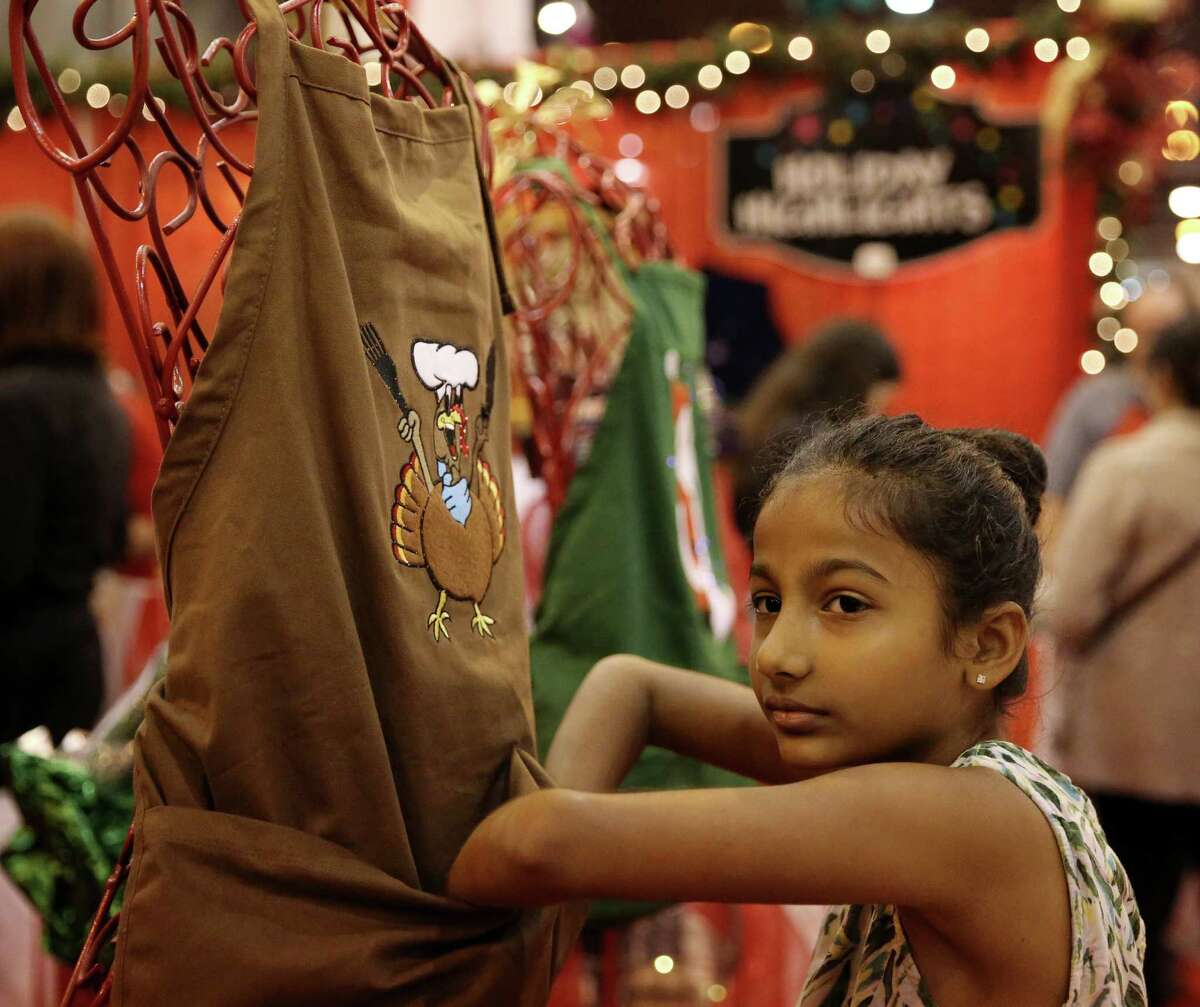 Sanam Patel, 9, checks out the lighting turkey apron at the Nutcracker Market at NRG Center Sunday, Nov. 13, 2016, in Houston. Sanam would like to give the apron to her 13-year-old cousin, who likes to cook, during their family Thanksgiving dinner.