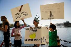 Mona M (second from left), 10 and Sage S., 10 (center) gather during an anti-Trump protest around Lake Merritt, in Oakland, California, on Sunday, Nov. 13, 2016.