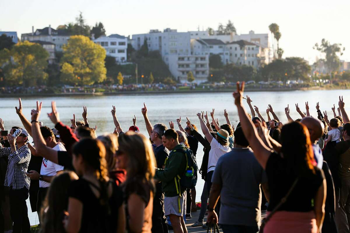 Hundreds hold up the peace sign as they gather during an anti-Trump protest around Lake Merritt, in Oakland, California, on Sunday, Nov. 13, 2016.