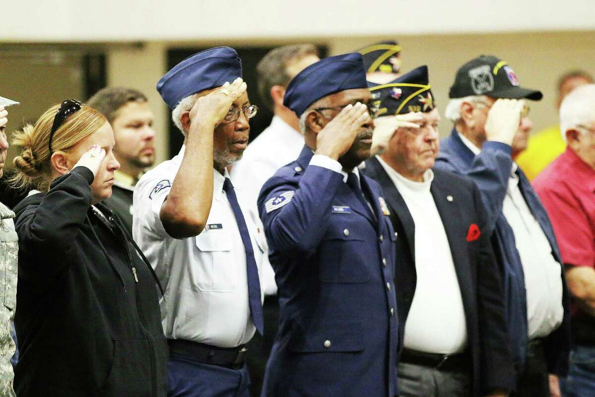 Veterans salute during the national anthem on Friday at the Liberty High School VeteranÂ?'s Day celebration. More than a couple dozen veterans attended the event on Nov. 11.
