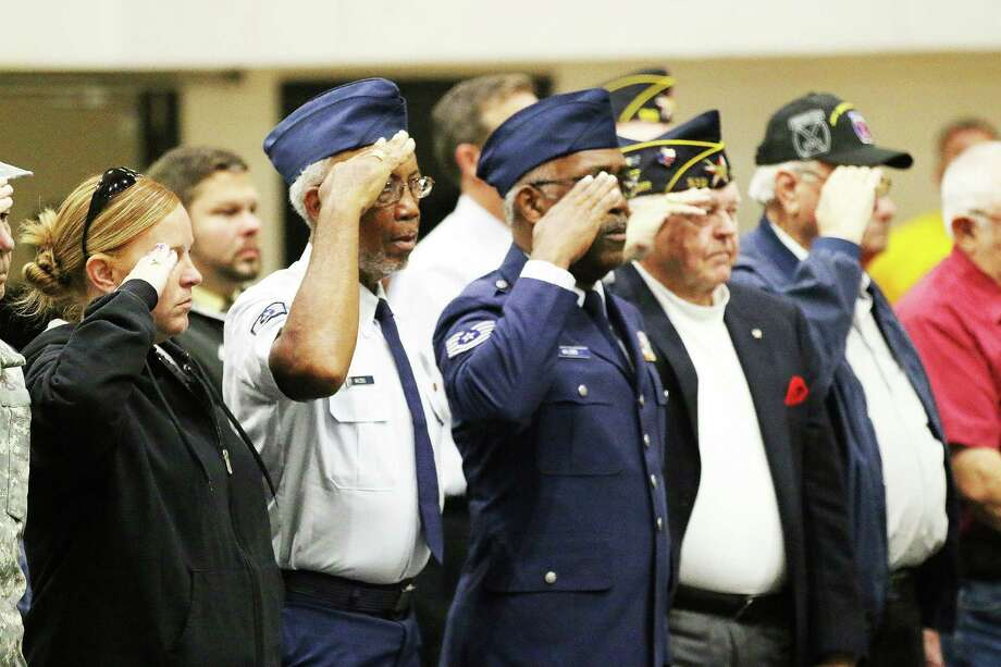 Veterans salute during the national anthem on Friday at the Liberty High School Veteran's Day celebration. More than a couple dozen veterans attended the event on Nov. 11. Photo: David Taylor