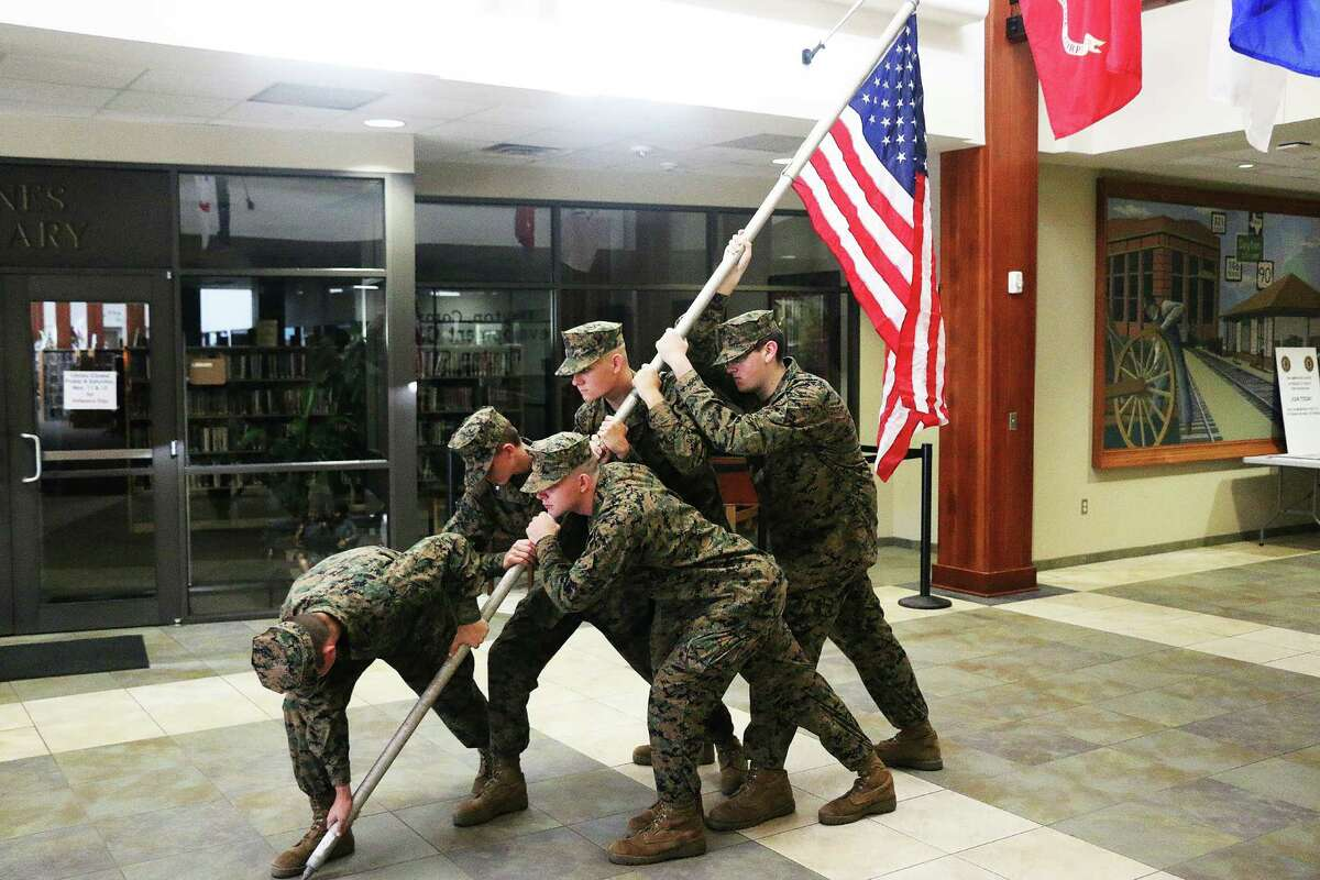 Dayton Junior ROTC members re-enact the raising of the U.S. flag on the shores of Iwo Jima in the front lobby of the Dayton Community Center. The stirring symbol greeted veterans as a reminder of their stunning success in the Pacific.