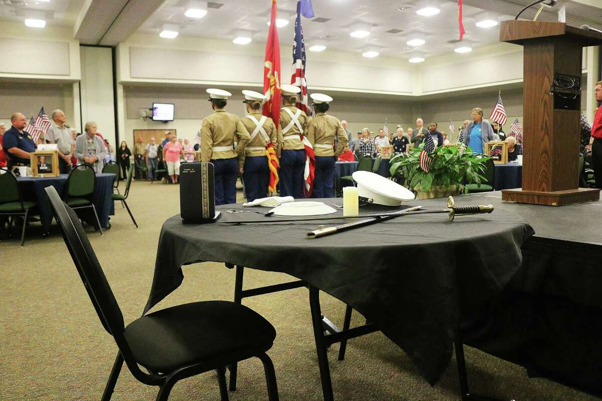 The Dayton Junior ROTC stands in the background in front of the Fallen Comrade Table, a remembrance of those who would not be joining their brothers in arms at the banquet.