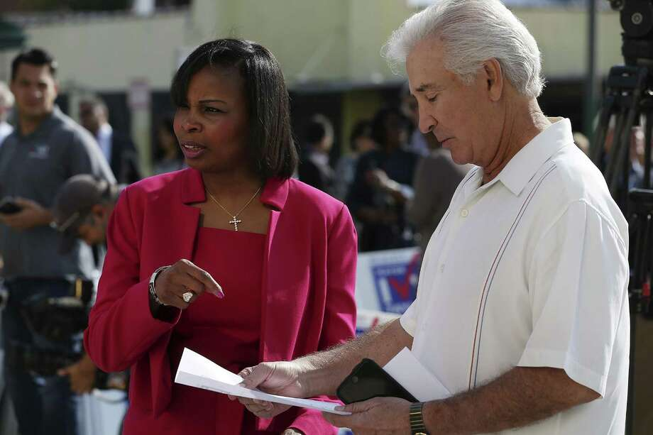San Antonio Mayor Ivy Taylor goes over details with auto dealer Ernesto Ancira during a gathering in front of CAST Tech High School, Sunday, Nov. 13, 2016. The mayor announced the start of her reelection campaign for a second term. Photo: JERRY LARA, Staff / San Antonio Express-News / © 2016 San Antonio Express-News