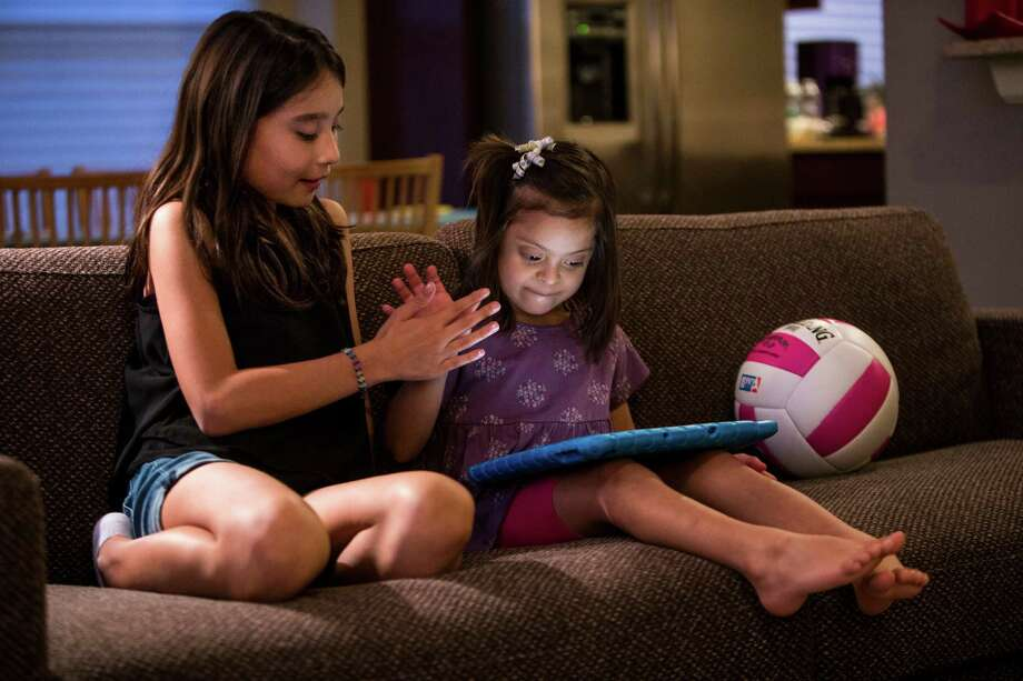 Six-year-old Miranda Pichardo, who has Down syndrome, high-fives with her sister Paloma, 10, as she plays on an iPad. Photo: Brett Coomer, Staff / © 2016 Houston Chronicle