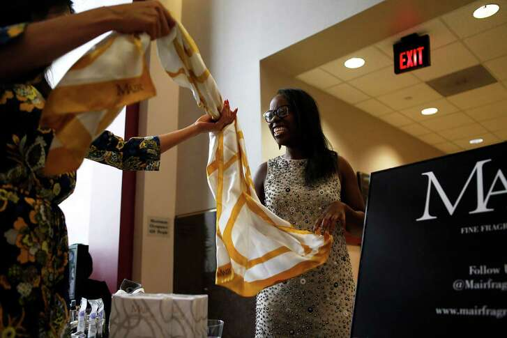 Mair Emenogu shows off one her silk scarves to attendees at the SWAG Expose entrepreneur event on Sunday in Houston. Emenogu currently sells fragrances and is expanding to include silk scarves next month.