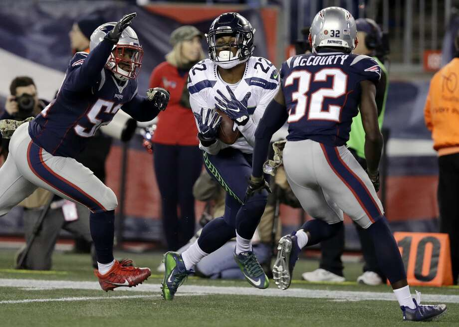 Seattle Seahawks running back C.J. Prosise (22) catches a pass between New England Patriots defenders Elandon Roberts, left, and Devin McCourty (32) during the second half of an NFL football game, Sunday, Nov. 13, 2016, in Foxborough, Mass. (AP Photo/Charles Krupa) Photo: Charles Krupa/AP