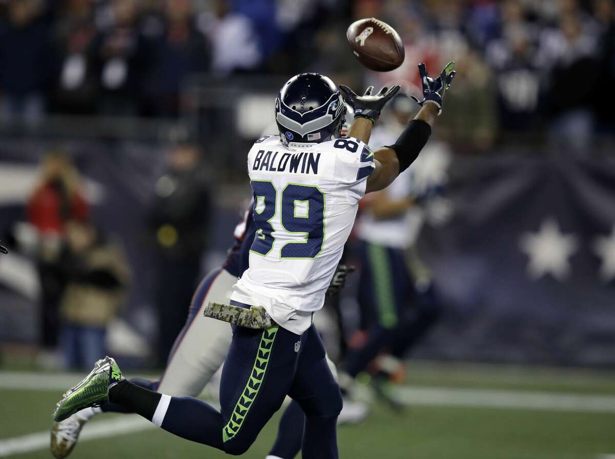 Seattle Seahawks wide receiver Doug Baldwin (89) catches a pass for his third touchdown of the game as New England Patriots defensive back Duron Harmon, rear, defends during the second half of an NFL football game, Sunday, Nov. 13, 2016, in Foxborough, Mass. (AP Photo/Charles Krupa)