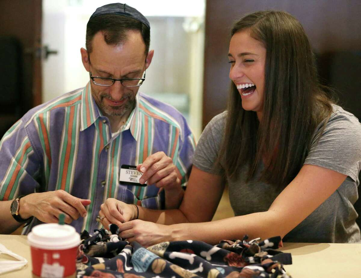 Melissa Reiner shows her father, Steven, how to make small blankets for Citizens for Animal Protection Service on Congregation Emanu El's Mitzvah Day on Sunday. It was the congregation's first time donating handmade blankets and chew toys to the animal service agency.
