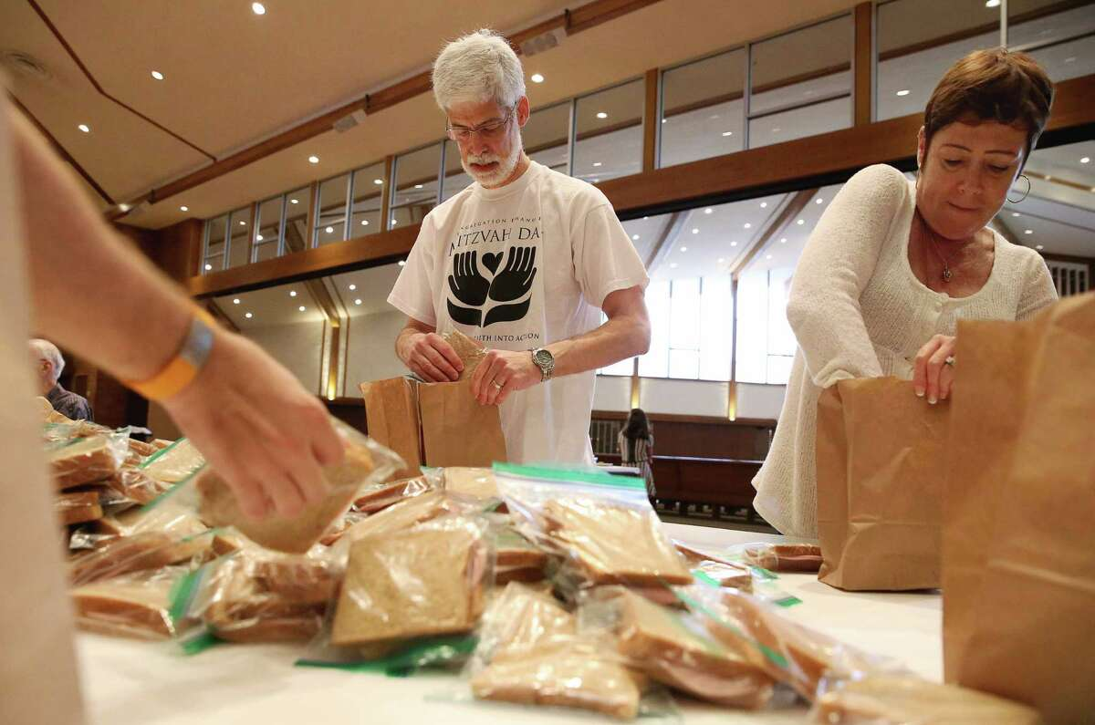 Congregation Emanu El members Paul Franks and Melia Cannata help prepare lunch bags for students on Mitzvah Day.