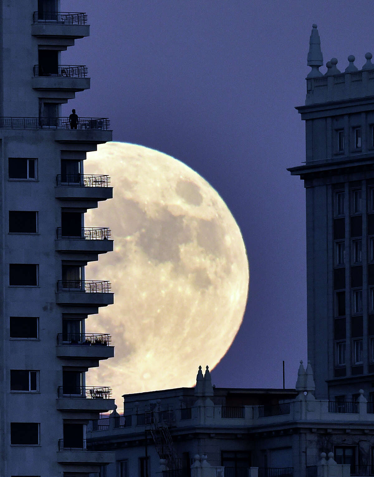 A man stands on a balcony of a building of Madrid as the moon rises in background, on November 13, 2016, on the eve of a
