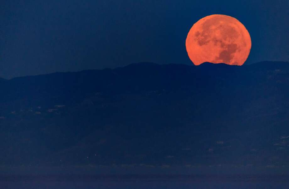 The moon sets during its closest orbit to the Earth since 1948 on November 14, 2016 in Venice Beach, California. The so-called Supermoon appears up to 14 percent bigger and 30 percent brighter as it comes about 22,000 miles closer to the Earth than average, though to the casual observer, the increase appears slight. Photo: Christopher Polk/Getty Images