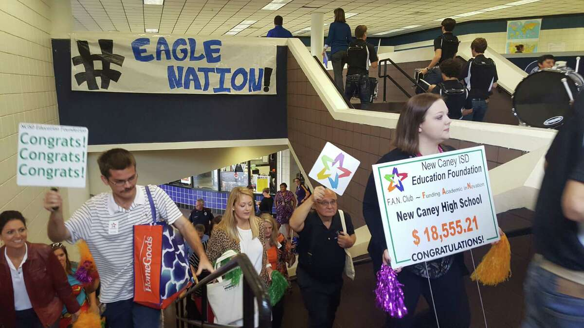 A parade of New Caney ISD Education Foundation supporters marches up the stairs at New Caney High School to surprise teachers with grants to fund educational resources Wednesday, Nov. 9.