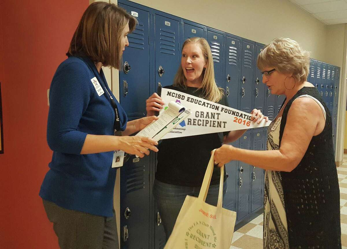 Michele Dykstra (left) and Kim Province (right) with the New Caney ISD Education Foundation surprise Infinity Early College High School teacher Jamie Siel with a grant for $4,994.01 to fund sensors and supportive equipment for scientific and biological coursework Wednesday, Nov. 9.