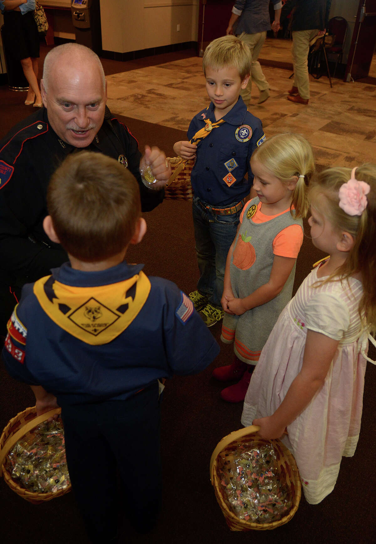 Harris County Pct. 4 Deputy Ken Perry, clockwise from top left, presents pins to Cub Scout Pack 1387 member Paul Marencic, 7, Elise Marencic, 4, Scarlett Clark, 4, and Cub Scout Pack 1387 member Graham Clark, 7, making them honorary Sherrif Deputies after they passed out American flag pins to guests at the Tribute to Veterans event at The Humble Civic Center on Nov. 9, 2016. (Photo by Jerry Baker/Freelance)