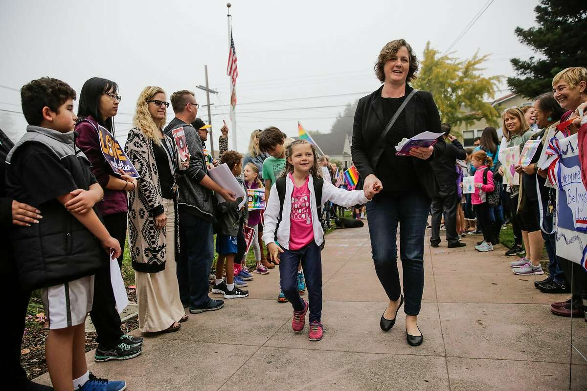 Monica Ware (right) walks her daughter Violet Schnitter (left), into Edison Elementary school on Monday morning, following an incident where racist graffiti was written on exterior of the school, in Alameda, California, on Monday, Nov. 14, 2016. Community members carried positive signs to greet students as they walked into school.