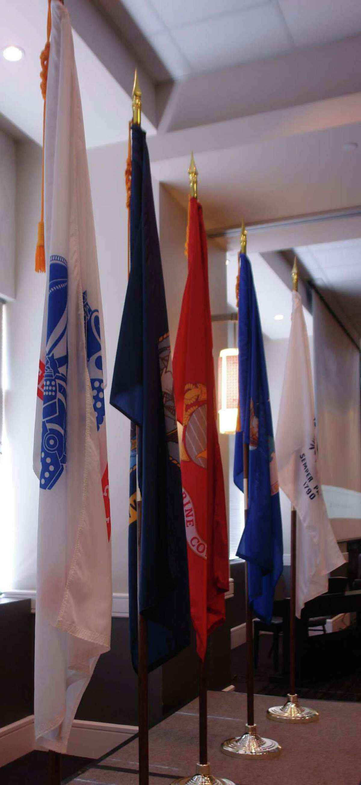 Flags from each branch of the military are displayed on the stage at the Salute to Veterans on Veterans Day on Friday, Nov. 11, at the Norris Convention Center in west Houston.