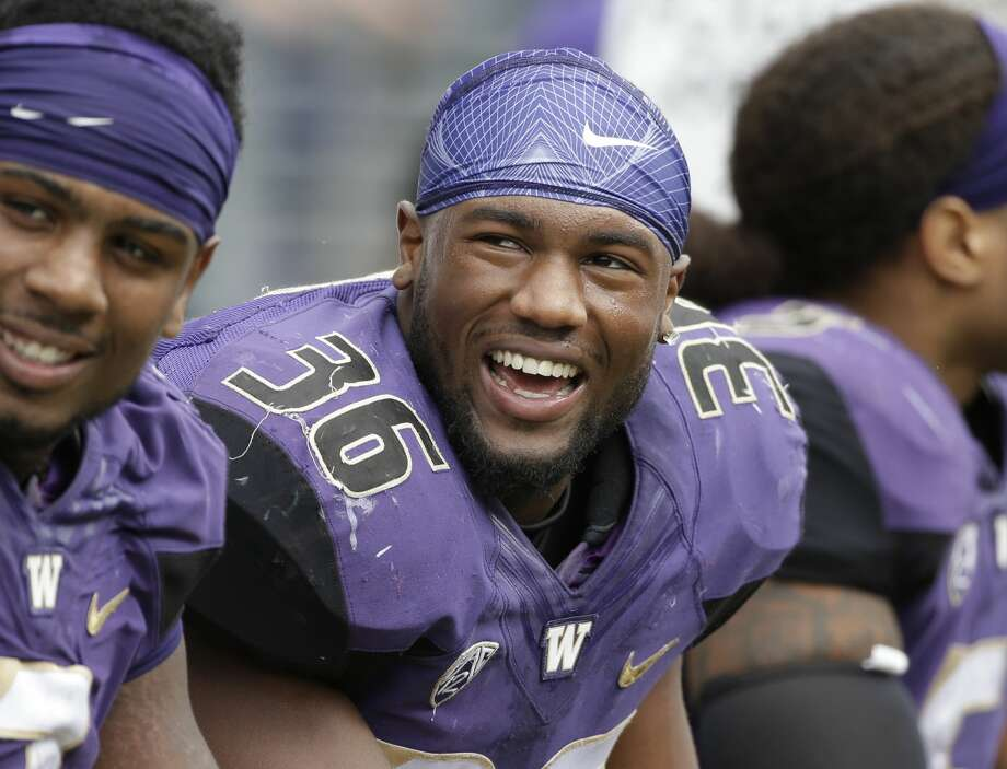 Washington's Azeem Victor smiles on the sidelines during an NCAA college football game against Rutgers, in Seattle. Photo: Elaine Thompson/AP