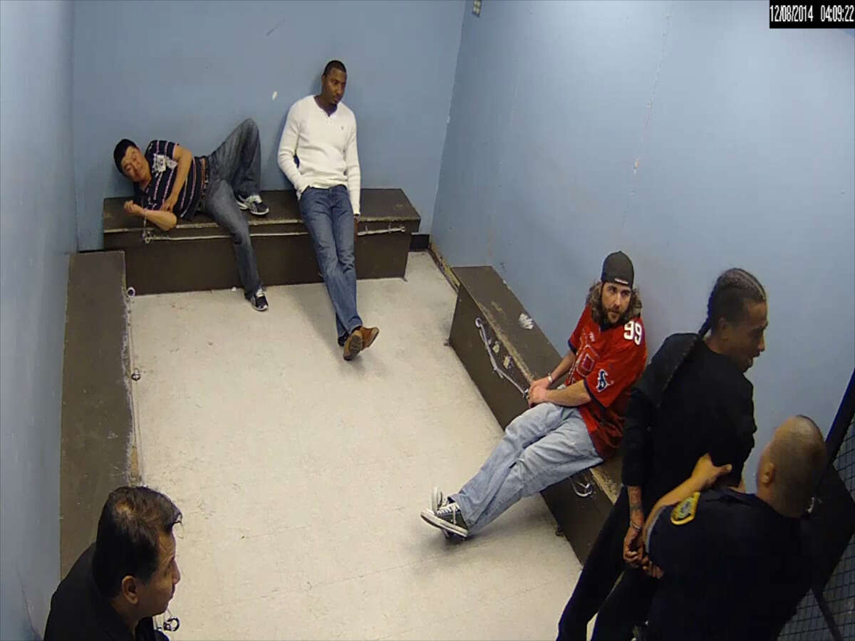 A screenshot of footage shows a Houston police officer bashing a man's head against a jail cell door, bloodying his face. Reuben Williams, the handcuffed man in the video, is now suing the Houston Police Department for excessive force for the 2014 incident.
