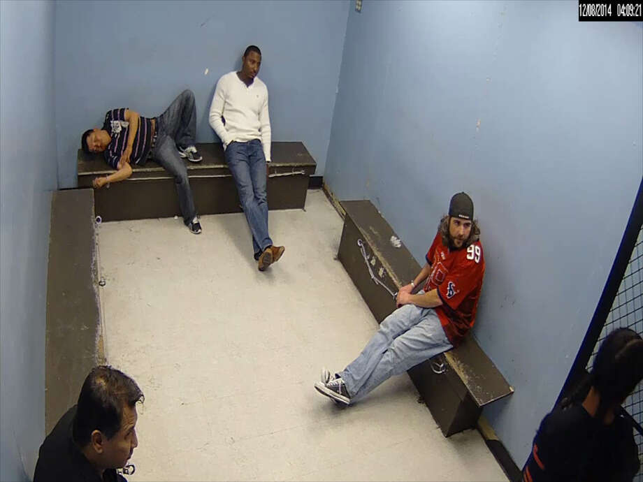 A screenshot of footage shows a Houston police officer bashing a man's head against a jail cell door, bloodying his face. Reuben Williams, the handcuffed man in the video, is now suing the Houston Police Department for excessive force for the 2014 incident. Photo: Reuben Williams/Courtesy To The Houston Chronicle