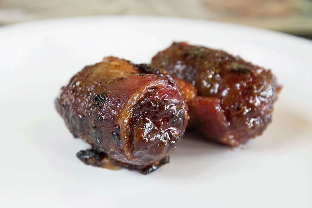 Goat cheese stuffed bacon wrapped dates in a brown sugar bourbon sauce