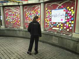 A woman reads messages posted on the Wall of Empathy on Monday morning at the 16th Street BART Station in San Francisco.