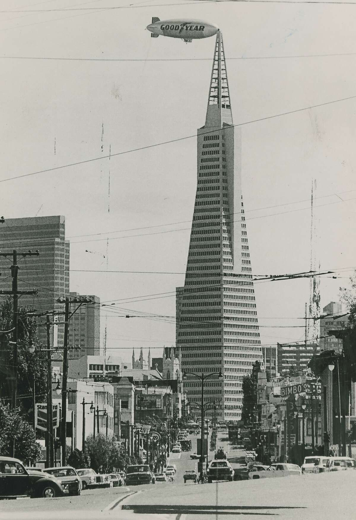 The Goodyear Blimp appears to be kissing the tip of the Transamerica Pyramid building in San Francisco. The photographer actually caught this image, in a split second, as the blimp was flying by, our King Kong to the Empire State Building. The photo is dated December 20, 1984. The Northbeach club, Bimbo, can be seen in the background.