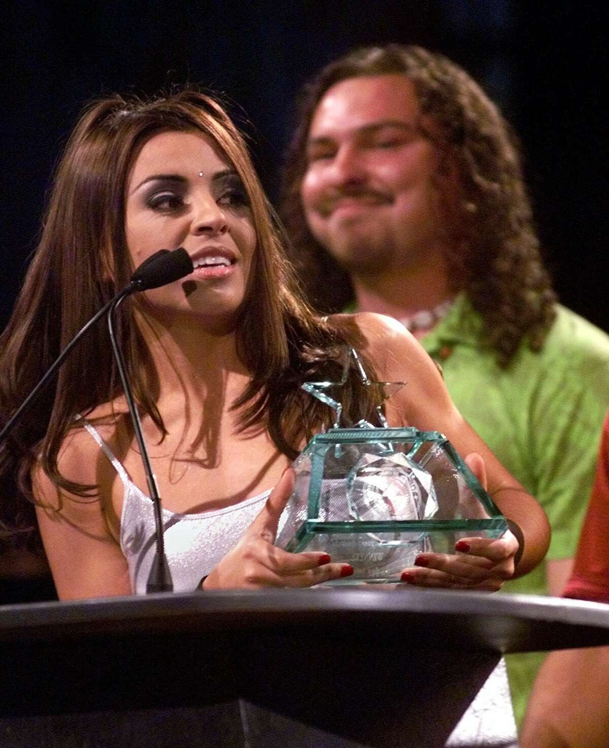 Elida Reyna accepts a Tejano Music Award at the Alamodome in San Antonio on Saturday, March 11, 2000, for her band Avante, which won in the category of Mexican Regional Song with 'Duele.' Percussionist Epi Martinez looks at the award from behind. (AP Photo/Express-News, Tom Reel)