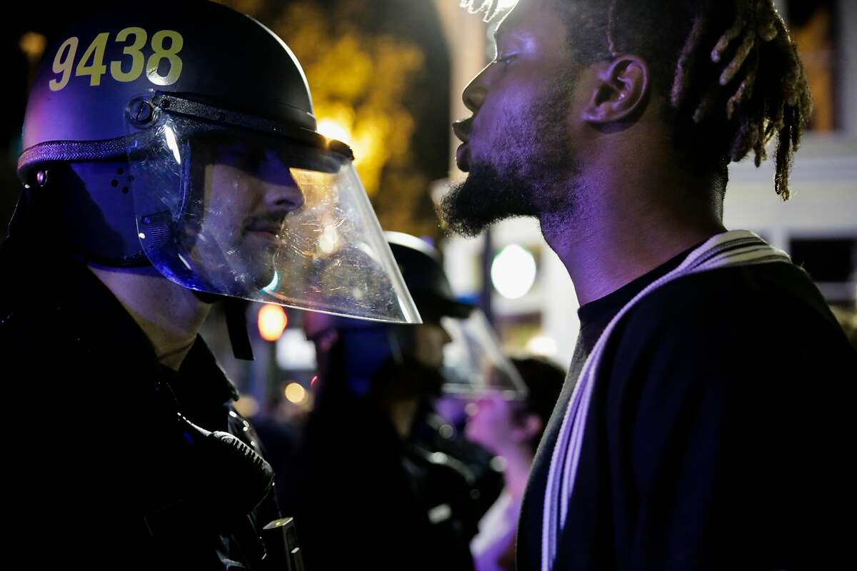A protester against president-elect Donald Trump yelled at a police officer during a demonstration in Oakland, California, U.S., November 9, 2016.
