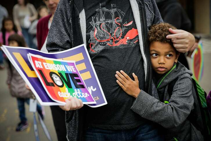 Farber Moody-LaLonde, 8 embraced his father Ryan LaLonde (left) while walking into Edison Elementary school on Monday morning, following an incident where racist graffiti was written on exterior of the school, in Alameda, California, on Monday, Nov. 14, 2016. Community members gathered outside the school to greet students with signs of positivity on Monday morning.