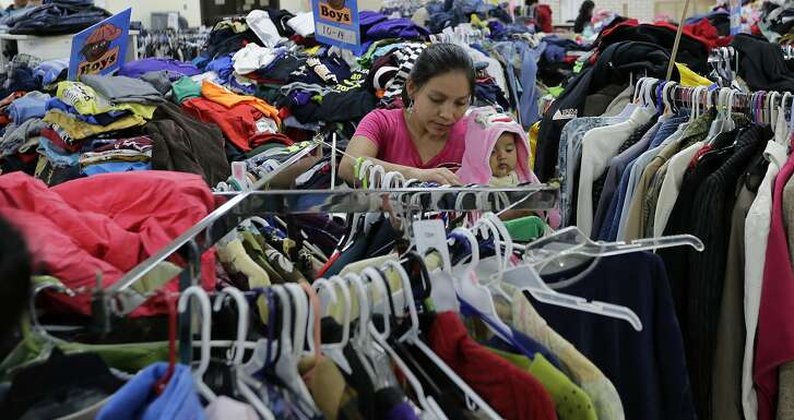 Central American migrants newly released after processing by the U.S. Customs and Border Patrol look for clothing at the Sacred Heart Community Center in the Rio Grande Valley border city of McAllen, Texas, Sunday, Nov. 13, 2016. President-elect Donald Trump is starting to sound a lot more like President Barack Obama on his stance on immigration and easing his pledge to build a wall across the Mexican border. (AP Photo/Eric Gay)