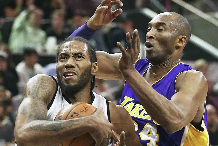 Spurs' Kawhi Leonard muscles his way past ex-Lakers star Kobe Bryant in February. Photo: Tom Reel /San Antonio Express-News / 2016 SAN ANTONIO EXPRESS-NEWS